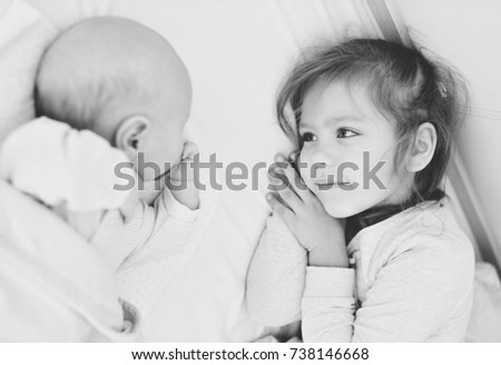 Little sister lookging at her newborn baby brother