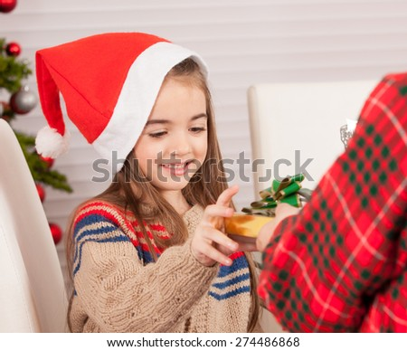 Little sister receiving Christmas gift from her brother. - stock photo