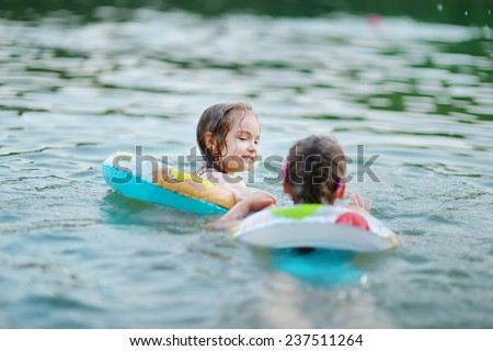 Little sisters having fun swimming in a lake at summer - stock photo