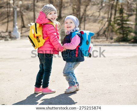 little sisters in a park in spring - stock photo