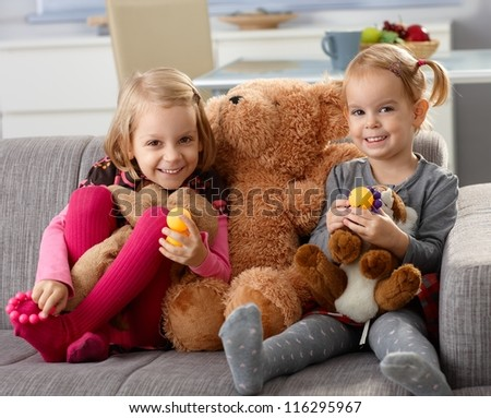 Little sisters smiling happily at home, sitting on sofa with big teddy bear.