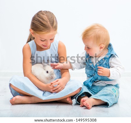 Little sisters with a rabbit in a basket - stock photo