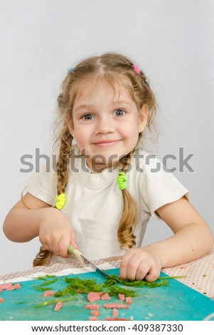 Little six year old girl trying to cut the greens at the kitchen table - stock photo