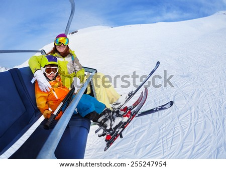 Little skier boy with mother lift on mountain - stock photo