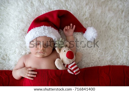 Little sleeping newborn baby boy, wearing Santa hat and pants, holding toy