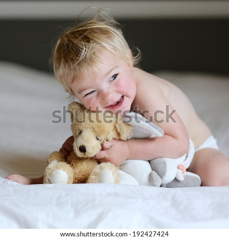 Little sleepy child, just awake blonde curly toddler girl, playing with teddy bear sitting indoors in bedroom on big parents bed on an early sunny morning