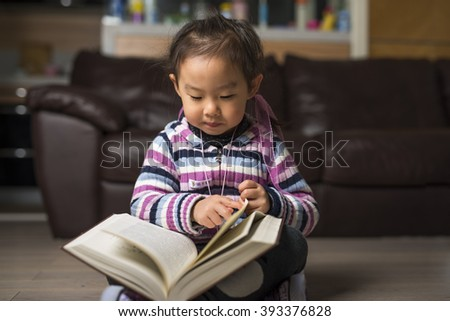 little smart girl reading a book