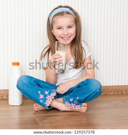little smiley girl drink the milk  on the floor - stock photo