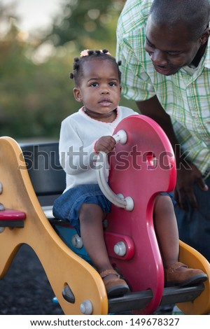 Little Smiling African American Girl Playing with Dad Outdoor