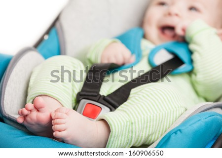 Little smiling baby child fastened with security belt in safety car seat - stock photo