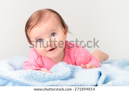 Little smiling baby girl lying on stomach, on blue blanket. She is wearing pink suit body and looking at camera - stock photo