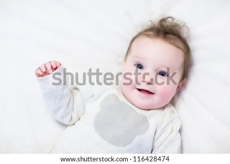 Little smiling baby in a knitted teddy bear sweater - stock photo