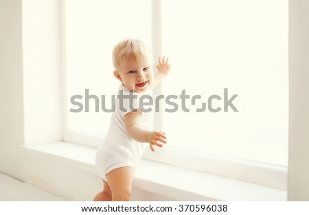 Little smiling baby in white room at home stands near window - stock photo