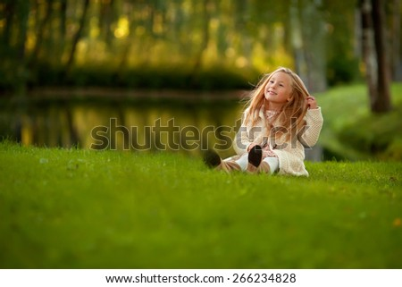 little smiling blond girl with long hair in the beige coat is sitting on the grass near the lake and touching her hair  - stock photo