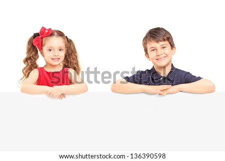 Little smiling boy and girl standing behind a blank panel isolated on white background - stock photo