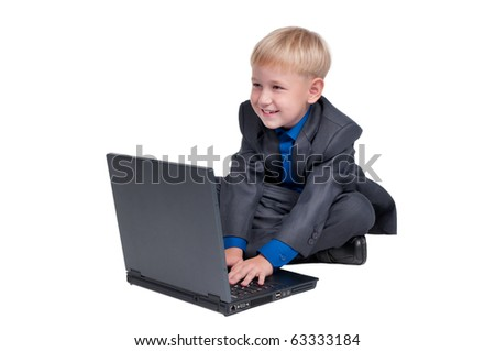 Little smiling boy dresses with gray suit and blue shirt sitting on the floor and browsing in the internet through computer (laptop) isolated on white background