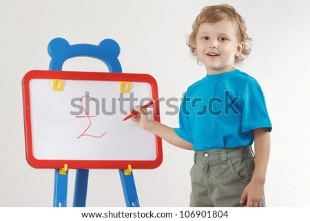 Little smiling boy drew a pound sign on the whiteboard - stock photo