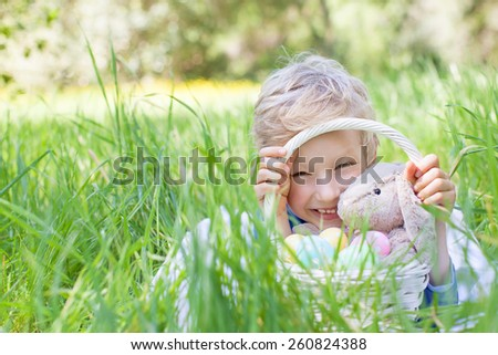 little smiling boy holding basket with easter eggs and bunny after egg hunt in the park lying in the grass - stock photo