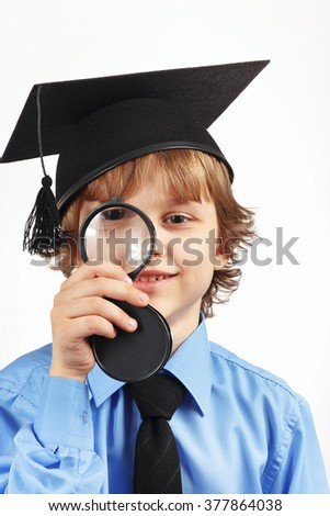 Little smiling boy in academic hat with a magnifying glass on a white background - stock photo