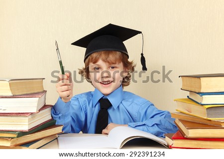 Little smiling boy in academic hat with rarity pen among the old books - stock photo