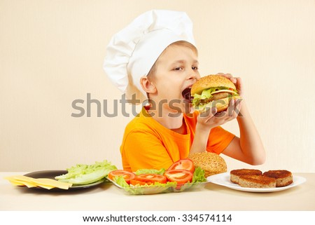 Little smiling boy in chefs hat is tasting the cooked hamburger - stock photo
