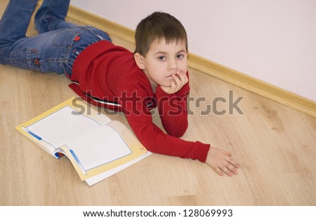 Little smiling boy is lying on a floor at home