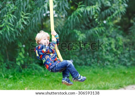 Little smiling boy of three years having fun on swing on sunny summer day, outdoors. Active sports with kids. - stock photo