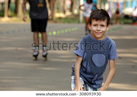 Little smiling boy on background roller skate children - stock photo