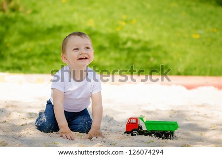 Little smiling boy playing with sand and toy on playground in summer