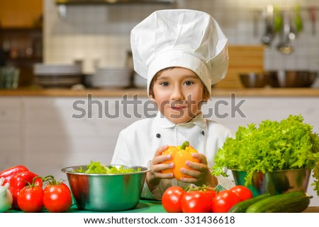Little smiling Chef boy preparing healthy food at kitchen. the concept of vegetarianism - stock photo