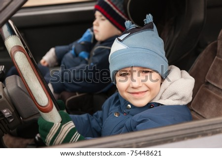 Little smiling child boy driving sport car vehicle