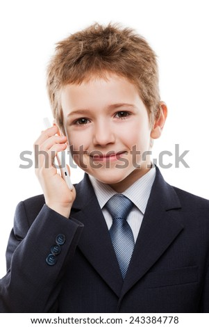 Little smiling child boy in business suit hand holding mobile phone or talking smartphone white isolated - stock photo