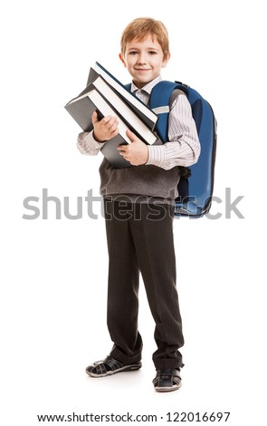 Little smiling child boy with school backpack holding education books in hands
