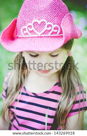 Little smiling cowgirl outdoors - stock photo