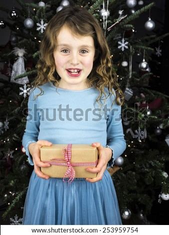 little smiling curly haired girl holding a traditional christmas present with christmas tree behind - stock photo