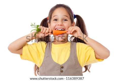 little smiling girl biting the carrot, isolated on white