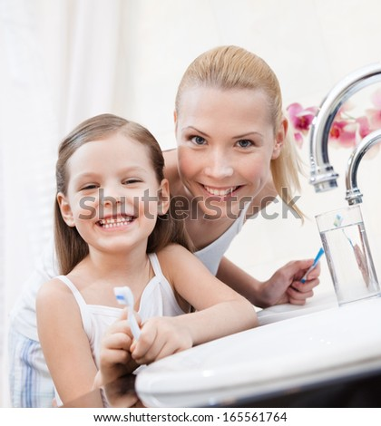 Little smiling girl brushes her teeth with her mom - stock photo