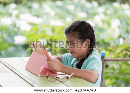 Little smiling girl enjoying modern generation technologies playing outdoors using tablet pc with touchscreen. - stock photo