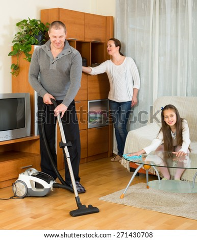 Little smiling girl helping happy parents to clean at home. Focus on man - stock photo