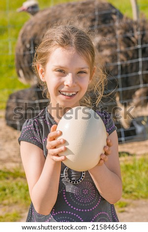 Little smiling girl holding large ostrich egg. - stock photo