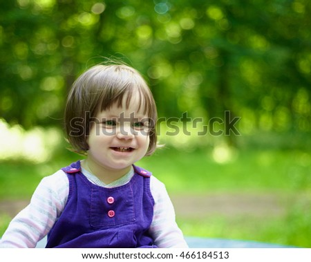 little smiling girl in a blue dress on nature