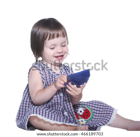 little smiling girl in a checkered dress holding a mug isolated on white background