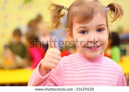 Little smiling girl in kindergarten shows sign ok - stock photo
