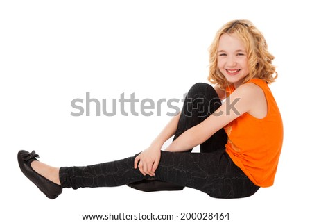little smiling girl in orange clothes and black shoes sitting over white background - stock photo
