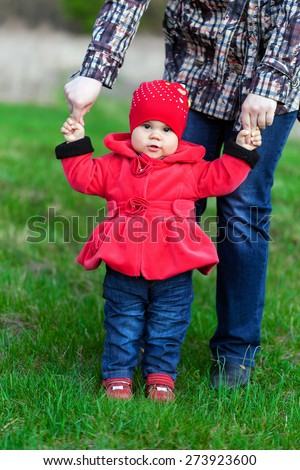 Little smiling girl in red coat is posing on the lawn. Her mother is teaching her daughter to walk - stock photo