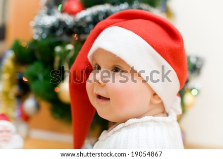 Little smiling girl in red Santa hat under christmas tree