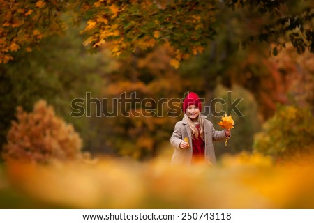 little smiling girl in the autumn park - stock photo