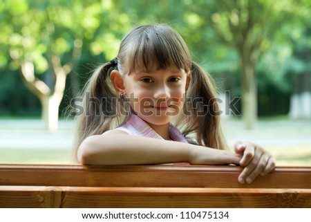 Little smiling girl on a park bench
