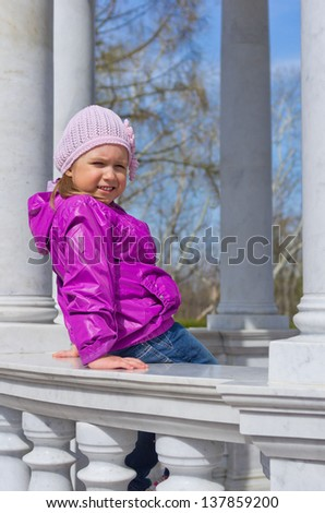 Little smiling girl on bench at park - stock photo
