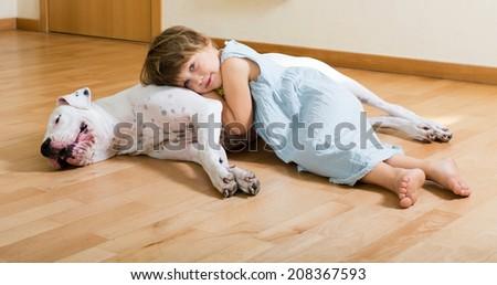 little smiling girl on the floor with dogo Argentino(focus on dog)